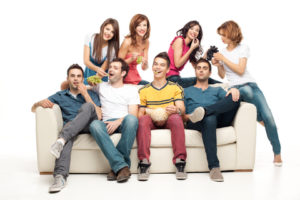 young group of friends sitting on couch eating